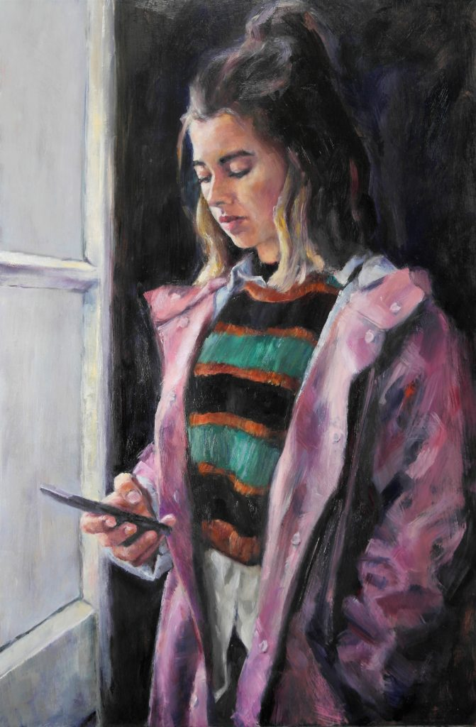 Andrea met mobiel bij het raam in roze regenjas