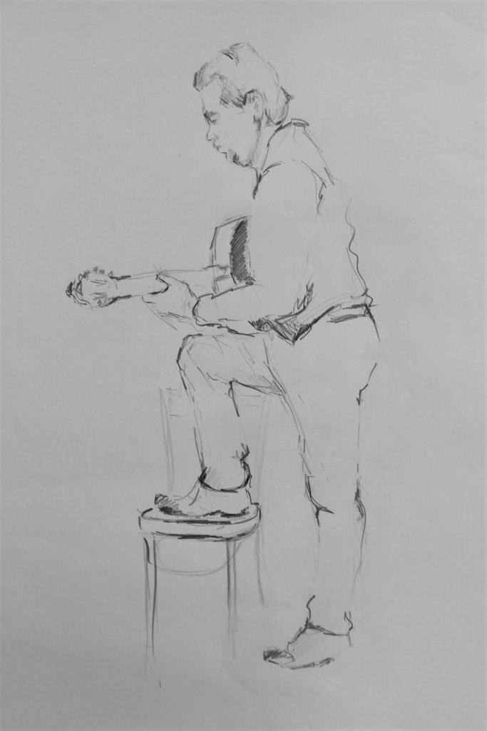 schets-gitarist-met-een-voet-op-stoel-potlood-op-papier